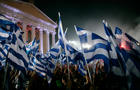 Supporters wave flags on May 3, 2012, as Greek New Democracy leader Antonis Samaras addresses a pre-election rally in Athens, Greece.