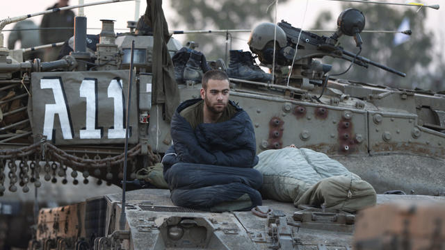 An Israeli soldier sits after he woke up atop a tank at a staging area near the Israel Gaza Strip Border, southern Israel, Thursday, Nov. 22, 2012.