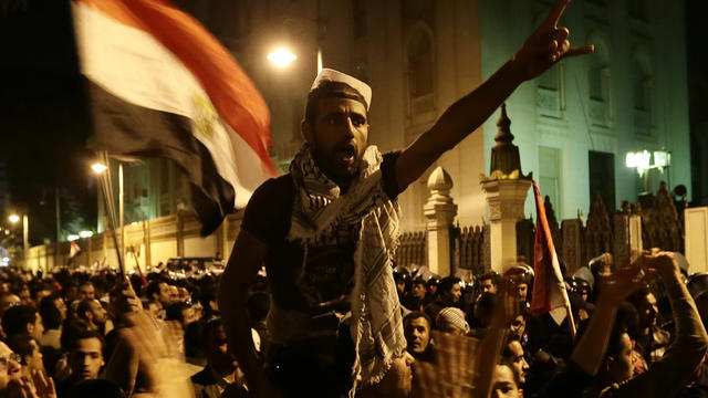 Egyptian protesters chant slogans against the Muslim Brotherhood and Egyptian President Mohammed Morsi outside the presidential palace after they broke a barbed wire barricade in Cairo Dec. 7, 2012.