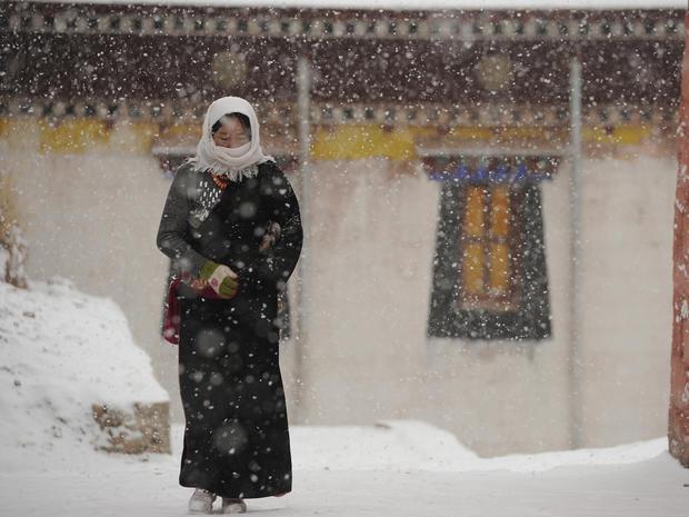 Tibetan pilgrim walks through Lajia Monastery in Qinghai province, China.