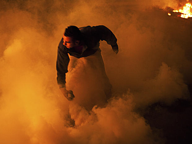 A protester prepares to throw a rock during clashes with security forces near Tahrir Square