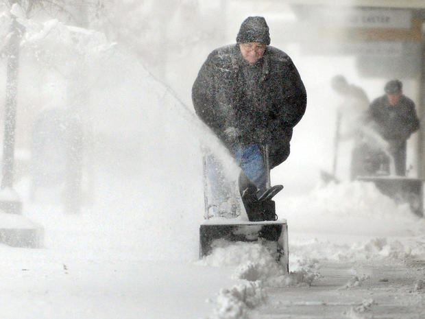 Chuck Carroll, center, uses a snowblower to clear the sidewalk in front of his business in downtown Salina, Kan., Feb. 21, 2013.