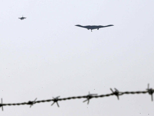 U.S. Air Force B-2 stealth bomber, center, flies over near the Osan U.S. Air Base in Pyeongtaek, south of Seoul, South Korea, March 28, 2013.