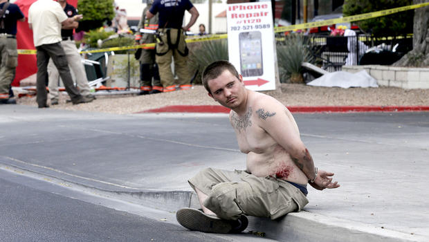 A man sits handcuffed on the sidewalk waiting to be escorted away by police after crashing a vehicle into a crowded restaurant, Monday, April 1, 2013, in Las Vegas.