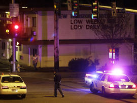 A Washington State Patrol trooper directs a driver away from a street blocked off several blocks from the scene of an overnight shooting that police said left five people dead, Monday, April 22, 2013, at an apartment complex in Federal Way, Wash.