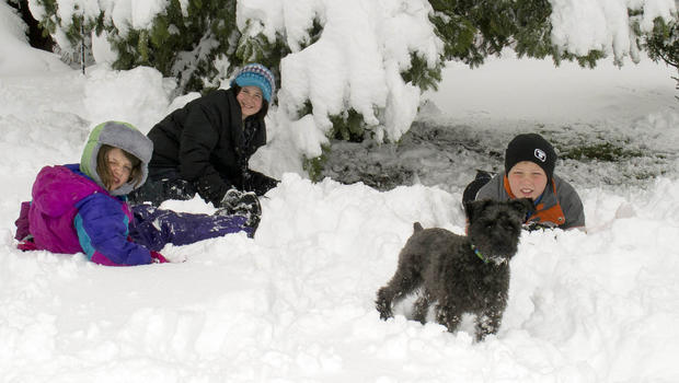 In this photo provided by Cory Howe Photography, Averie and Emma Howe, from left, and Sam Pfieffer, right, enjoy a school snow day as they pose Thursday, May 2, 2013 in Owatonna, Minn. A May snowstorm dumped heavy snow across parts of Minnesota and Wisconsin, resulting in dozens of school districts canceling classes.