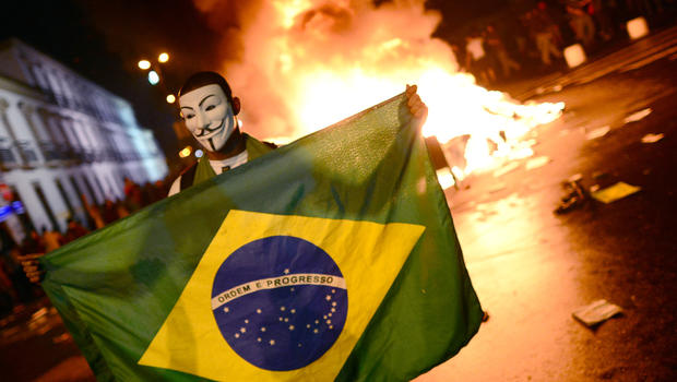 A demonstrator wearing a Guy Fawkes mask holds a Brazilian national flag during clashes in downtown Rio de Janeiro on June 17, 2013, after a protest against higher public transportation fares and the use of public funds to finance international football tournaments.