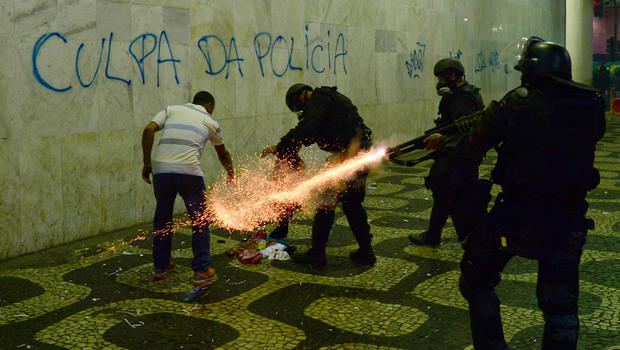 Anti riot police officers fire tear gaz in a corridor after clashes erupted during a protest against corruption and price hikes, on June 20, 2013, in Rio de Janeiro. Brazilians took to the streets again Thursday in several cities on a new day of mass nationwide protests, demanding better public services and bemoaning massive spending to stage the World Cup.