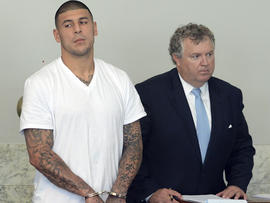 New England Patriots tight end Aaron Hernandez, left, stands with his attorney, Michael Fee, right, in Attleboro District Court June 26, 2013, in Attleboro, Mass.