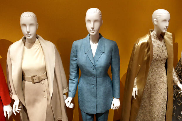 """An Oscar de la Renta pantsuit, center, worn by Former first lady Hillary Rodham Clinton, is displayed next to other creations by the designer at the Clinton Presidential Library in Little Rock, Ark., Monday, July 8, 2013. The """"Oscar de la Renta: American Icon"""" exhibit is on display at the Clinton library until Dec. 1."""