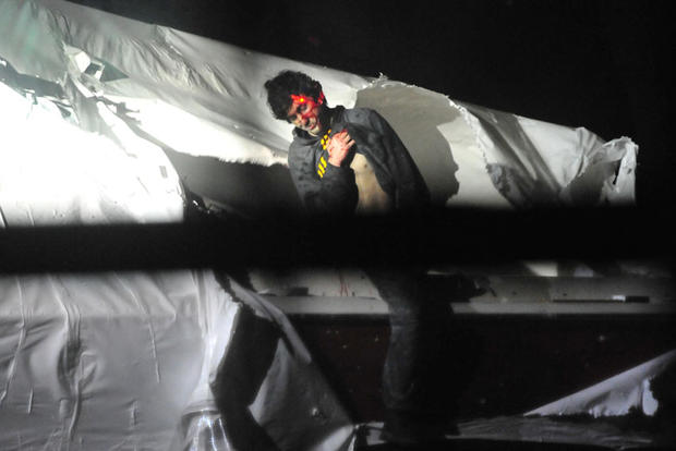 Dzhokhar Tsarnaev emerges from the boat he was hiding in in Watertown, Mass.