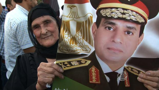A woman holds a sign of Gen. Abdel Fattah al-Sisi's face.