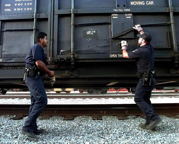 U.S. Customs agents prepare to open a train car north of Laredo, Texas, on June 28, 1999. The intense manhunt for the railroad killer had intensified train car searches.