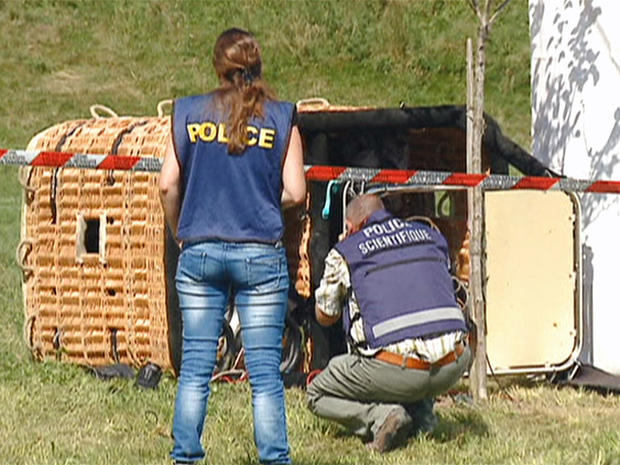 Swiss police examine the basket of a hot air balloon which crashed in the town of Montbovon