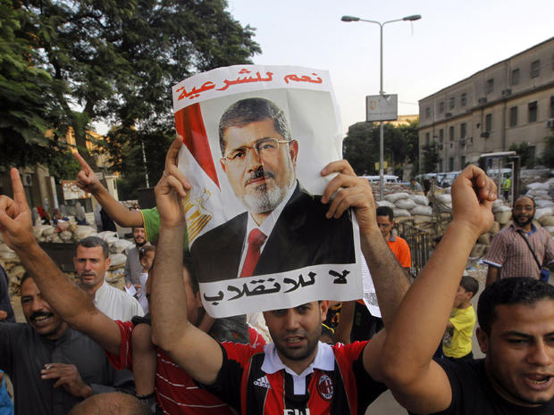 Supporters of Egypt's ousted President Mohammed Morsi walk through makeshift barriers to a sit-in at Nahda Square, which is fortified with multiple walls of bricks, tires, metal barricades and sandbags, where protesters have installed their camp near Cairo University in Giza, southwest of Cairo, Egypt, Saturday, Aug. 10, 2013.