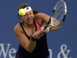 Marion Bartoli, from France, returns against Simona Halep, from Romania, during a match at the Western & Southern Open tennis tournament Aug. 14, 2013, in Mason, Ohio.