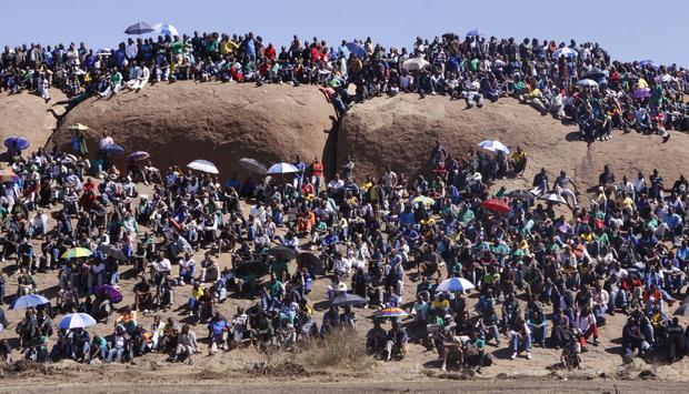 People attend a commemoration service for the striking platinum miners that were killed a year ago, in Marikana