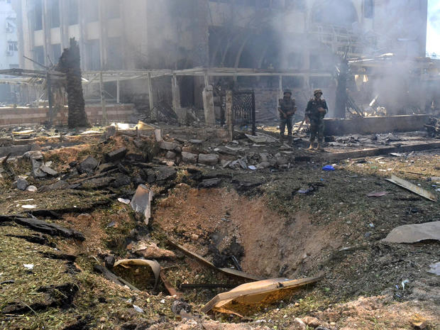 Lebanese army soldiers stand next to a blast crater outside of a mosque in the northern city of Tripoli, Lebanon, Aug. 23, 2013.