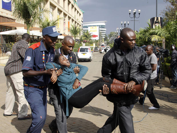 A security officer helps a wounded woman outside the Westgate Mall in Nairobi, Kenya, Sept. 21, 2013, after gunmen threw grenades and opened fire during an attack that left multiple people dead and dozens wounded.
