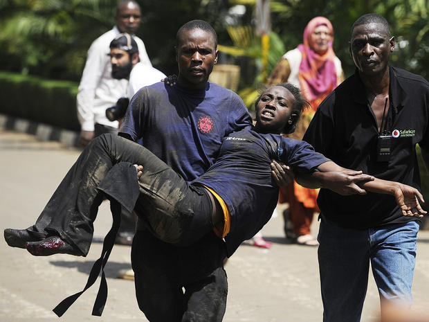 A Kenyan woman is helped to safety after masked gunmen stormed an upmarket mall and sprayed gunfire on shoppers and staff Sept. 21, 2013, in Nairobi, Kenya.