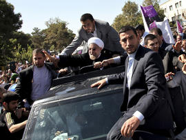 Iranian President Hasan Rouhani, center, waves to supporters upon his arrival from the U.S. near the Mehrabad airport in Tehran, Iran, Sept. 28, 2013.