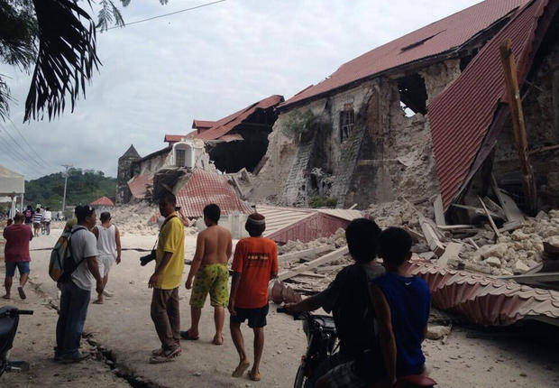 People walk past the damaged Church of San Pedro in the town of Loboc, in the Bohol province of the Philippines, after a major earthquake struck the region