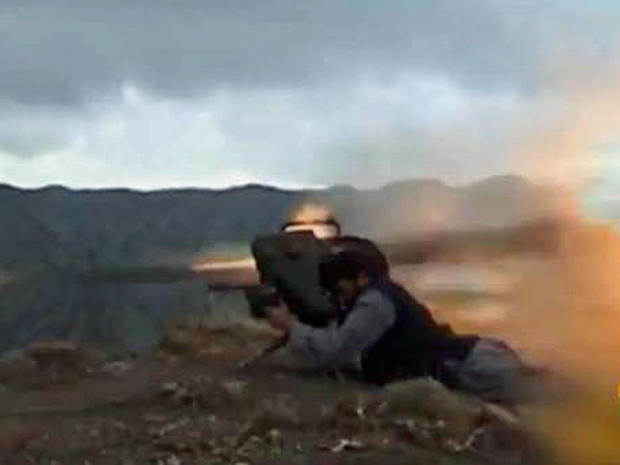 An militant from the Afghan Taliban launches a should-fired rocket