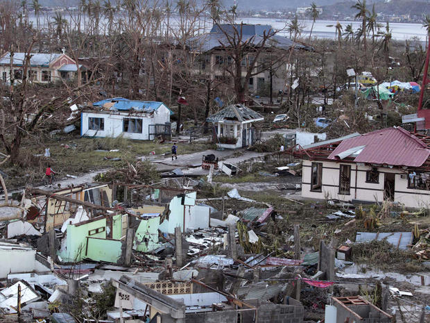A resident walks by remains of houses after powerful Typhoon Haiyan slammed into Tacloban on hardest-hit Leyte Island in the Philippines Nov. 9, 2013.