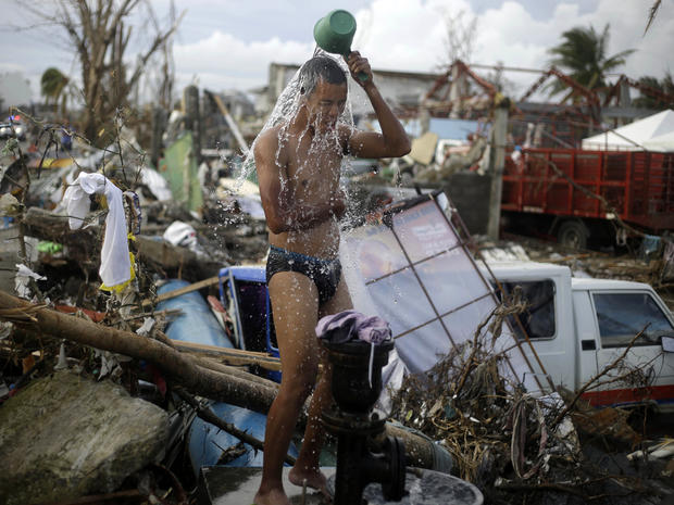 A man takes a shower amid rubble in an area badly affected by Typhoon Haiyan in Tacloban, Philippines, Nov. 13, 2013.