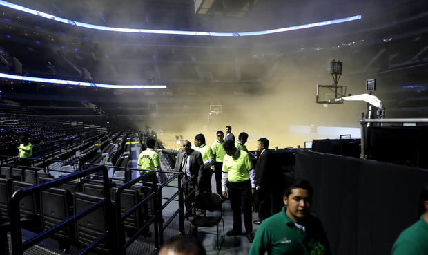 People leave as smoke engulfs the basketball court during a regular season NBA match between the Minnesota Timberwolves and the San Antonio Spurs in Mexico City