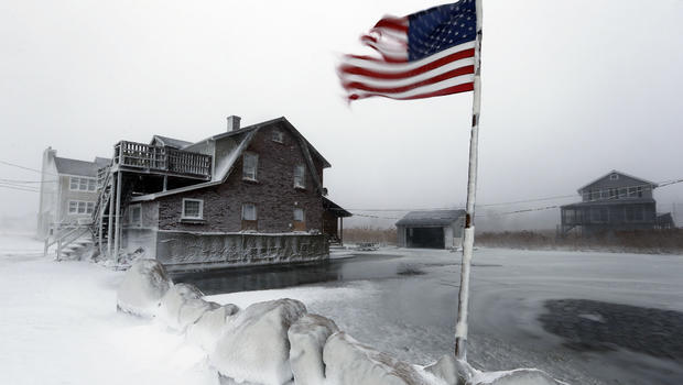 A tattered flag flies by a flooded yard along the shore in Scituate, Mass., Jan. 3, 2014.
