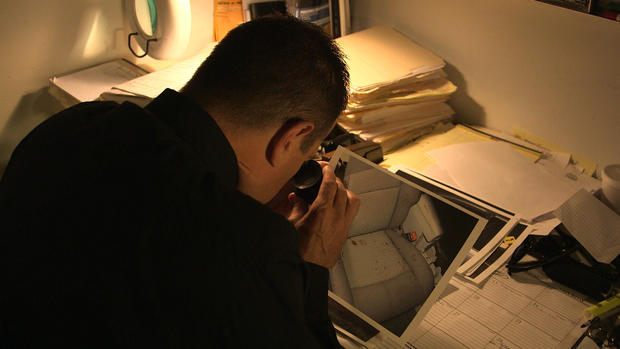 Det. Wagner takes a close look at photos of blood in the Schirmer's car after the crash.