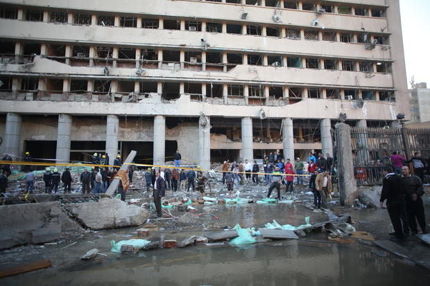 Egyptian police officers and firefighters gather at the Egyptian police headquarters after a blast in downtown Cairo