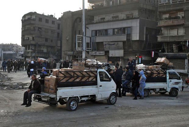 In this photo released by the Syrian official news agency SANA, trucks carry U.N. supplies at the besieged refugee camp of Yarmouk on the southern edge of the Syrian capital of Damascus
