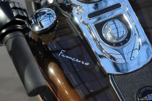 Pope Francis' signature is seen on the tank of a 2013 Harley-Davidson Dyna Super Glide Custom