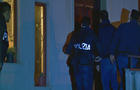 Italian police officers enter a residence near the port city of Goia Tauro during raids targeting members of the 'ndrangheta crime syndicate