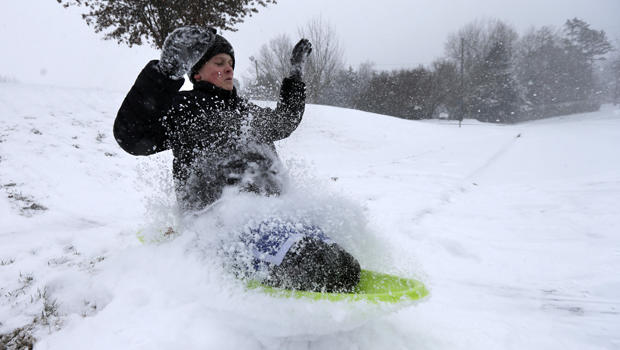 Stephen Clark, 12, hits a ramp made of snow as he sleds near his home in Charlotte, N.C., Feb. 12, 2014, as a winter storm moves into the area.