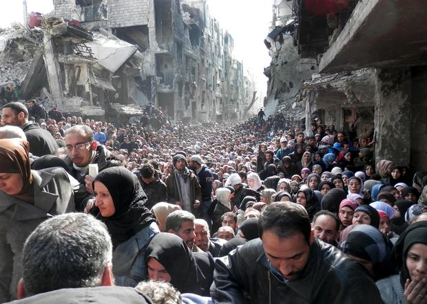 Palestinian residents of the Yarmouk camp in Damascus, Syria, queue for food aid