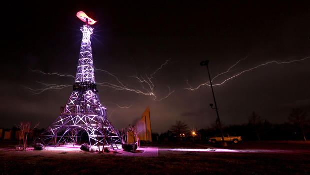 Lightning rips through the night sky April 3, 2014, behind a replica Eiffel Tower in Paris, Texas, as a severe thunderstorm moved through the southern part of Lamar County, bringing high winds, rain and hail.