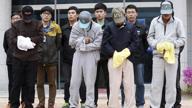 Crew members of the sunken Sewol ferry stand outside a court in Mokpo, South Korea, after investigators sought warrants of their arrest at the court April 26, 2014.