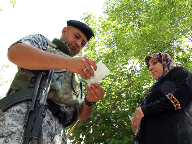 A member of the Iraqi security forces checks identities as voters arrive to cast their ballot in Iraq's first parliamentary election since U.S. troops withdrew at a polling station in Baghdad's Sadr City district