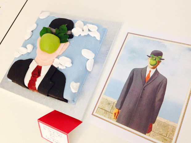 "A cake inspired by Rene Magritte's ""The Son of Man"" is seen next to a picture of the painting."