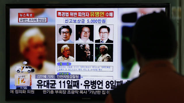 A TV news program shows the reward poster for billionaire Yoo Byung-eun at the Seoul Train Station