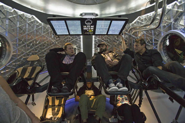 SpaceX CEO Elon Musk (L) sits with guests inside the Dragon V2 spacecraft after it was unveiled in Hawthorne