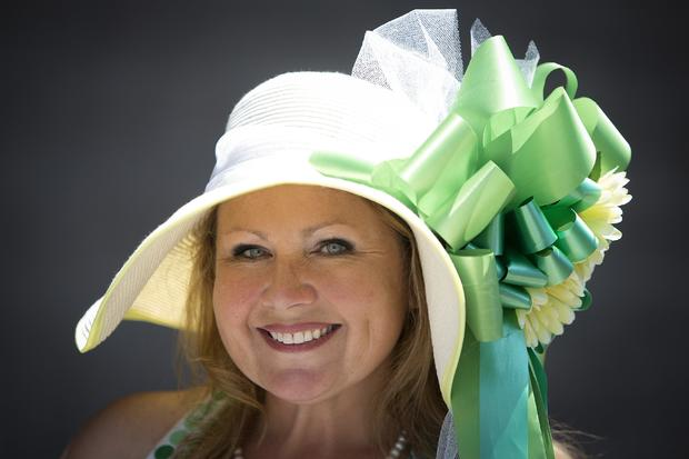 Brooke Maiello poses for a portrait with her colorful hat before the 146th running of the 2014 Belmont Stakes in Elmont, New York, June 7, 2014.