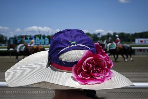 A woman stands on the rail as horses make their way for the third race at Belmont Park before the 2014 Belmont Stakes in Elmont, New York, June 7, 2014.
