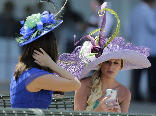 Two ladies enjoy the atmosphere in their hats prior to the 146th running of the Belmont Stakes at Belmont Park in Elmont, New York, June 7, 2014.