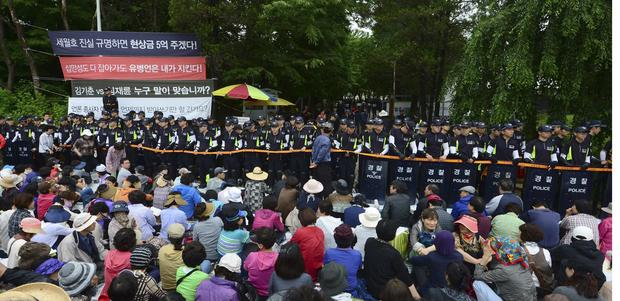 South Korean policemen stand guard in front of the main gate of the Evangelical Baptist Church premises, as church believers sit in front of the police barricade, in Anseong.