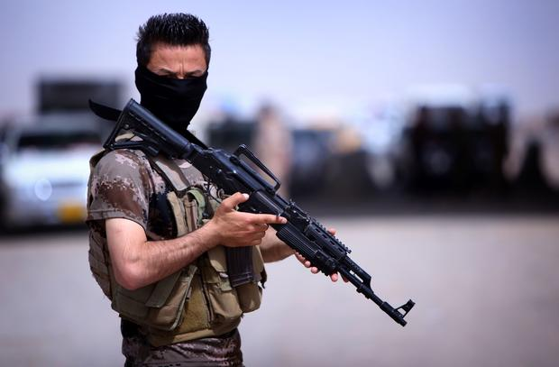 A masked Pershmerga fighter from Iraq's autonomous Kurdish region guards a temporary camp set up to shelter Iraqis fleeing violence in the northern Nineveh province on June 13, 2014.