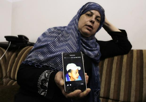Suha, mother of Mohammed Abu Khudair, shows a picture of her son on her mobile phone at their home in Shuafat